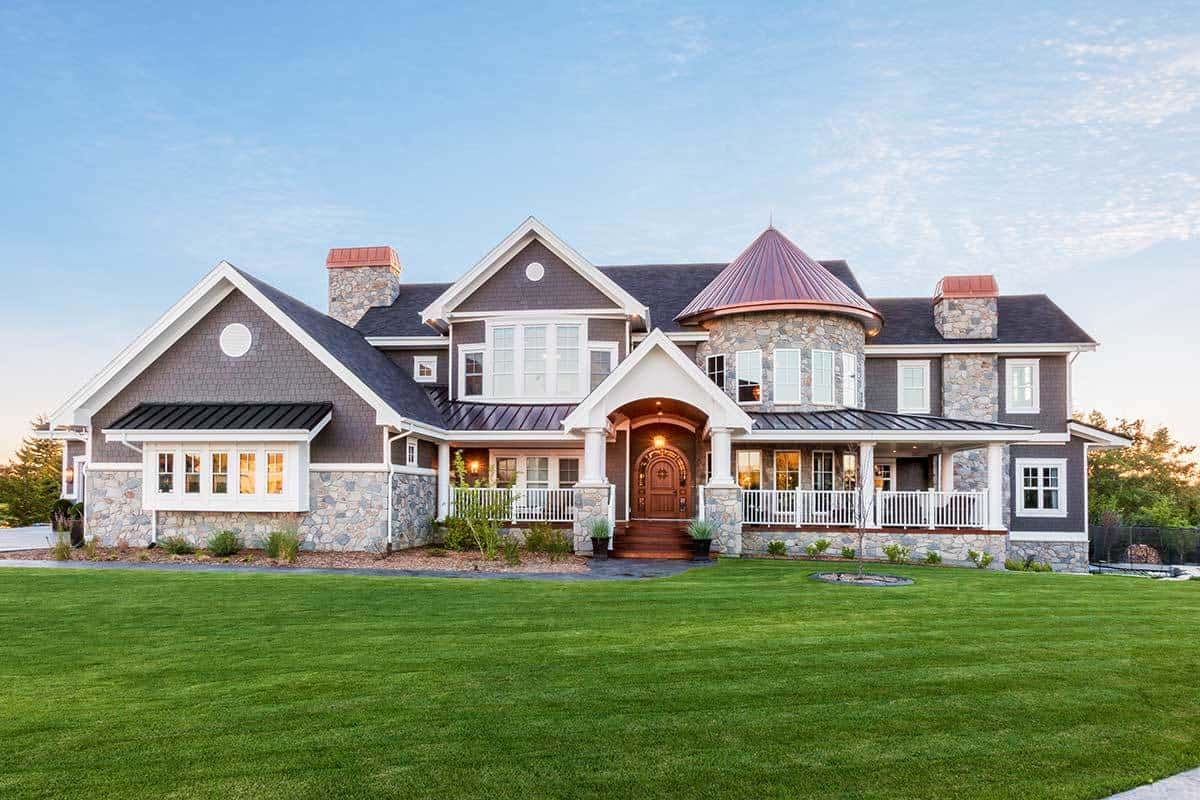 This is a full view of the front of the shingle-style home that has gray textured exterior walls that pair well with the stone mosaic wall accents. These are then elevated by the surrounding well-manicured grass lawn and an asphalt walkway.