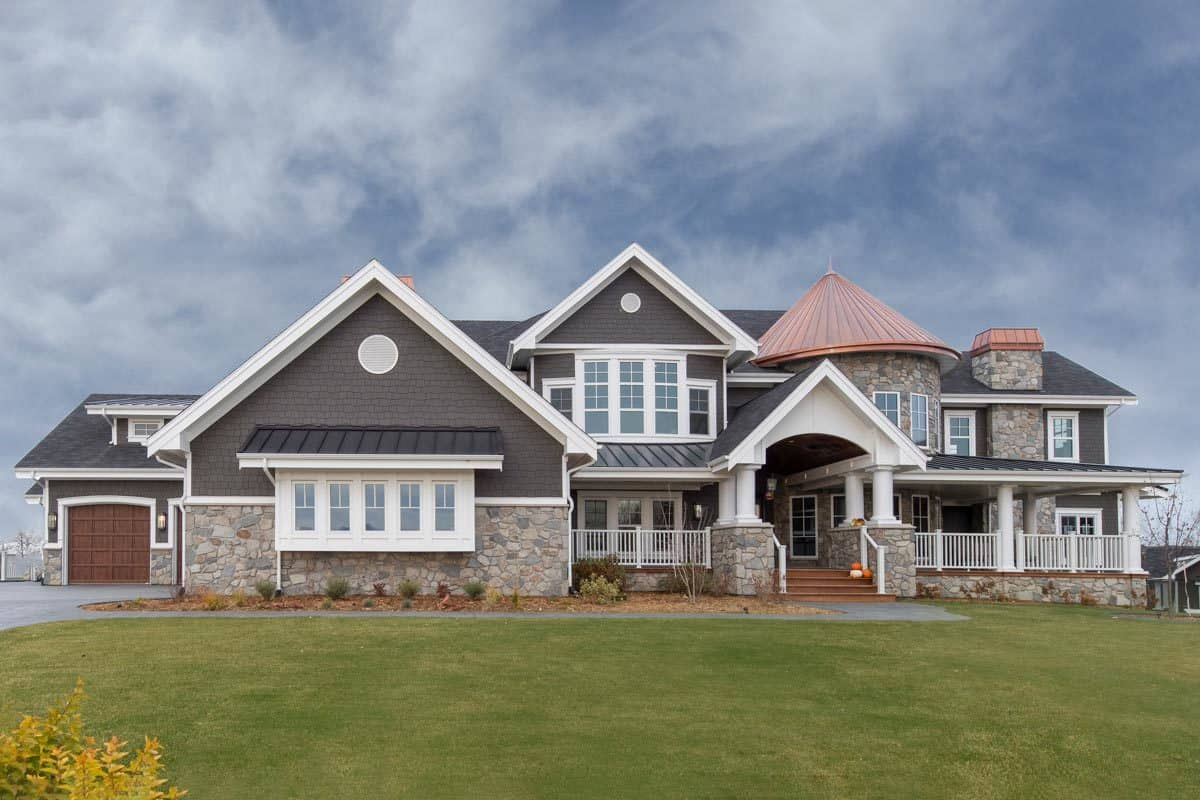 Home's front show showing the cedar shake and stone exterior, wide covered front porch, and an eye-catching turret.