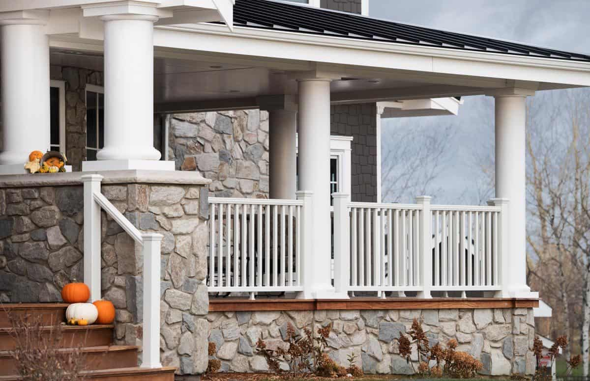 A closer look at the covered front porch framed with white railings and decorative columns.