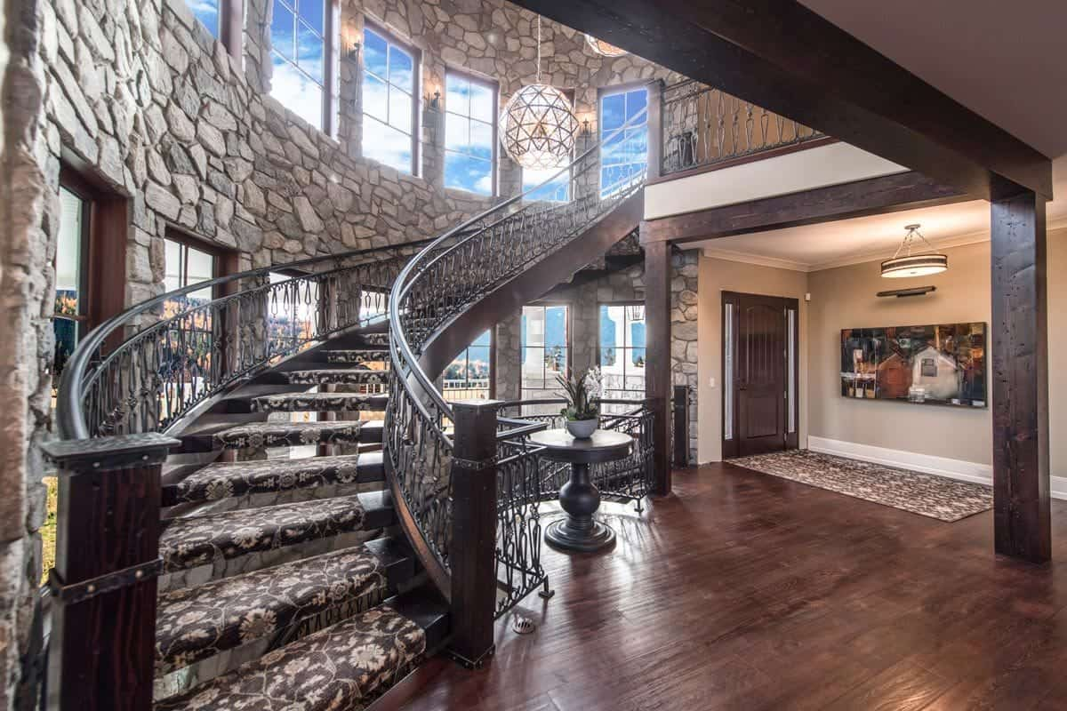 The foyer features an intricate winding staircase illuminated by oversized spherical chandeliers.