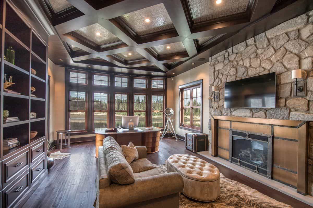The study has dark hardwood flooring, a stone accent wall, and a stunning coffered ceiling fitted with recessed lights.