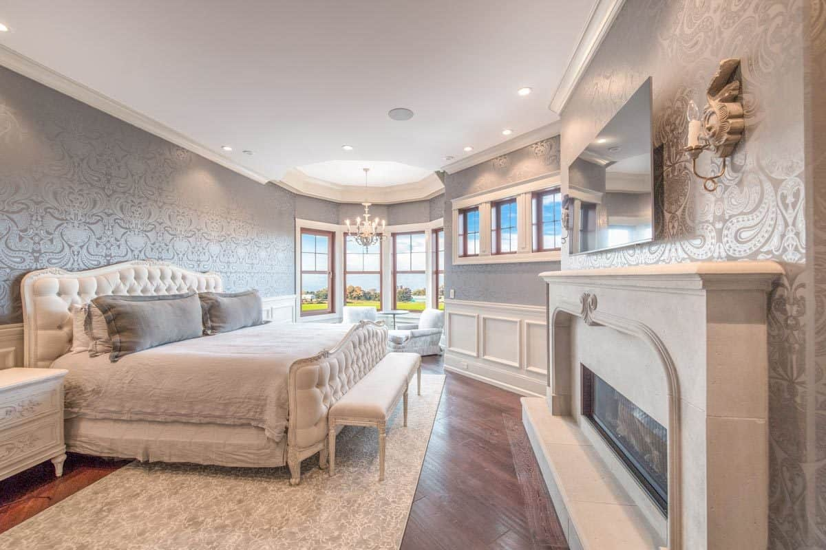 Primary bedroom with a white tufted bed, gray patterned wallpaper, modern fireplace, and a sitting area placed by the bay window.