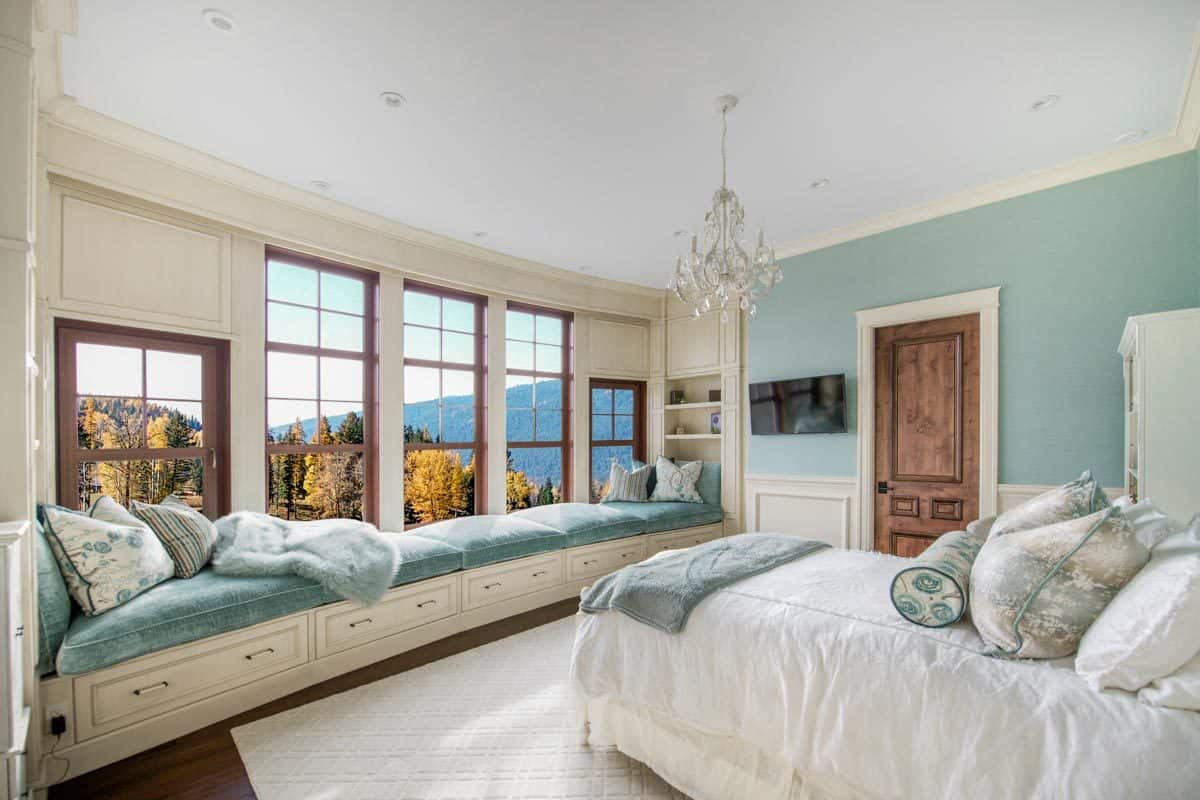This bedroom offers a single bed, crystal chandelier, wall-mounted TV, and a long window seat with a magnificent mountain view.