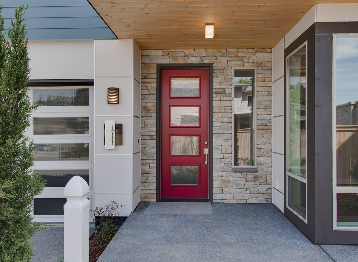 Home entry featuring a red glazed front door fitted against the stone wall.