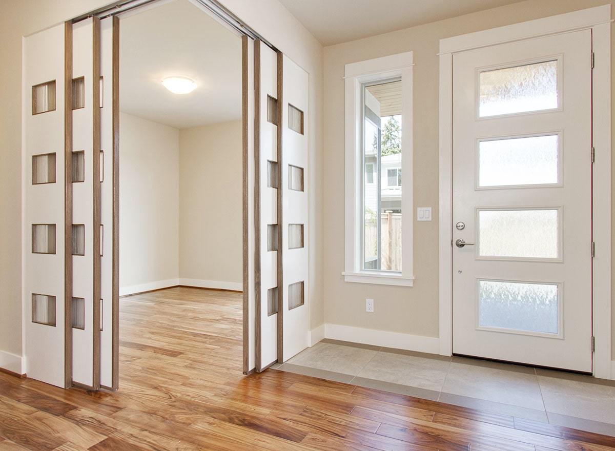 Foyer with a white entry door and natural hardwood flooring. Sliding doors on the side open to the den.