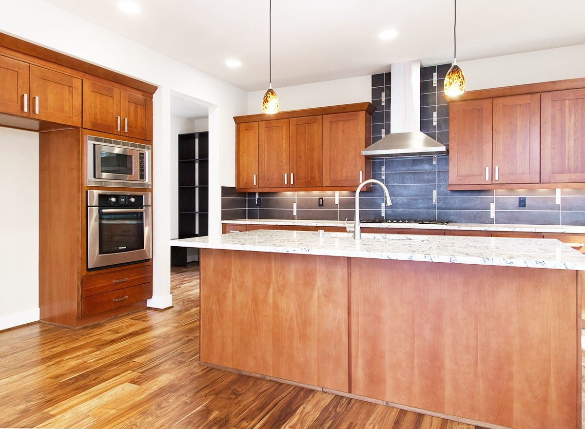 The kitchen is equipped with stainless steel appliances, marble countertops, wooden cabinetry, and an undermount sink fitted on the central island.