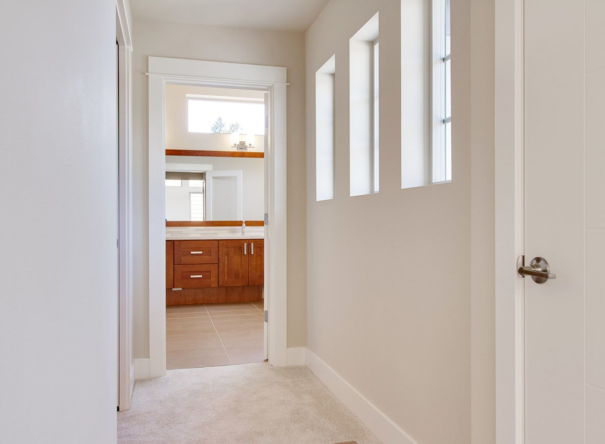 This hallway leads to the walk-in closet on the side and the primary bathroom ahead.