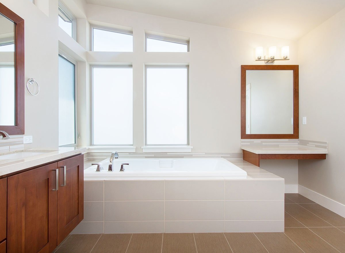 Next to the bathtub is a built-in vanity with a quartz countertop and a wooden framed mirror.