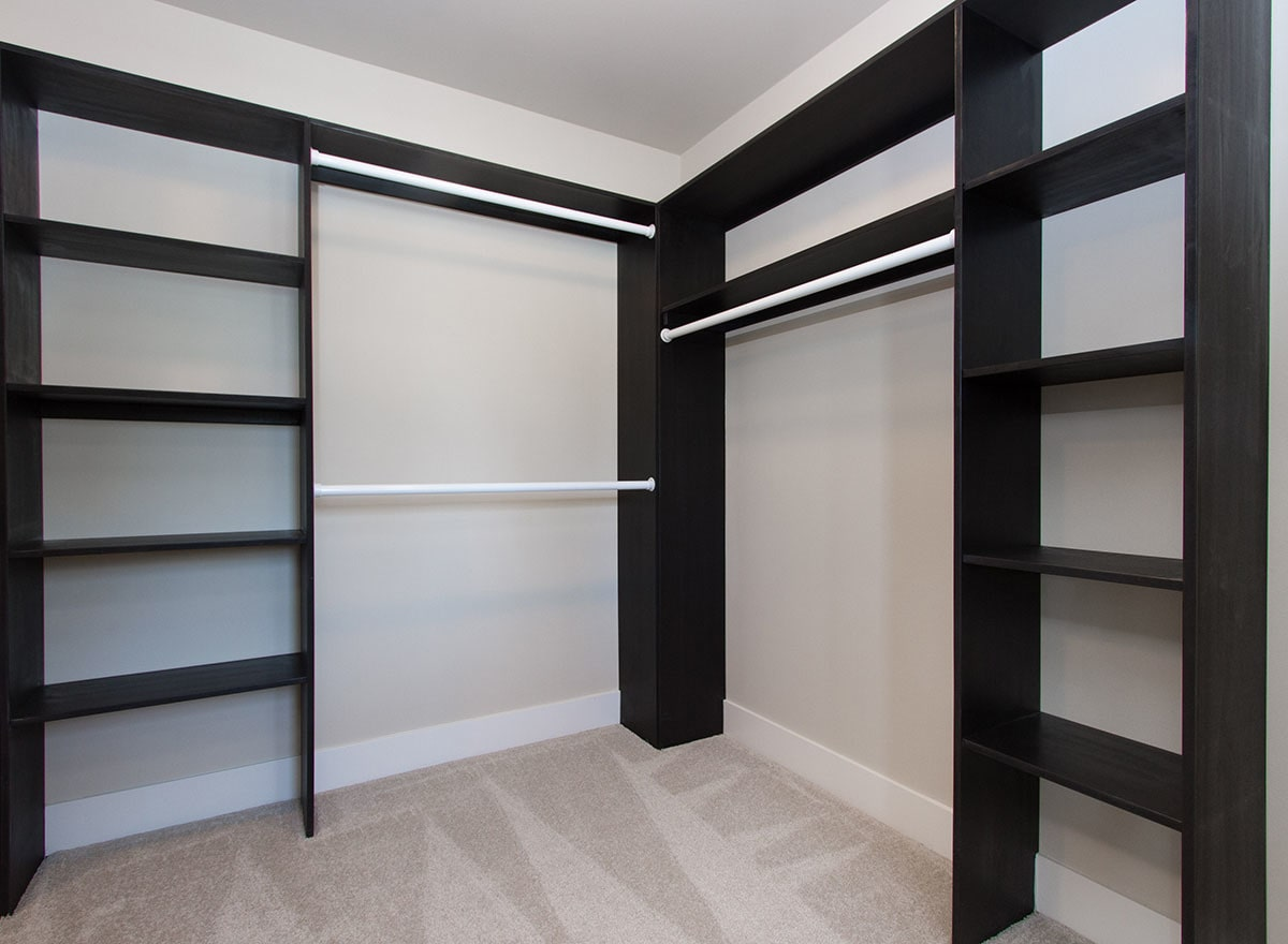 The walk-in closet is filled with black shelvings and built-in pole racks.