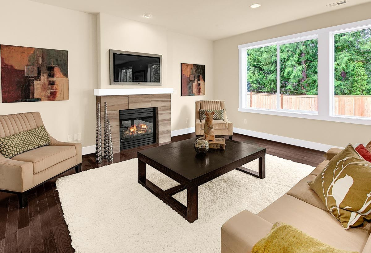 Living room with beige seats, a dark wood coffee table, and a glass-enclosed fireplace with a wall-mounted TV on top.