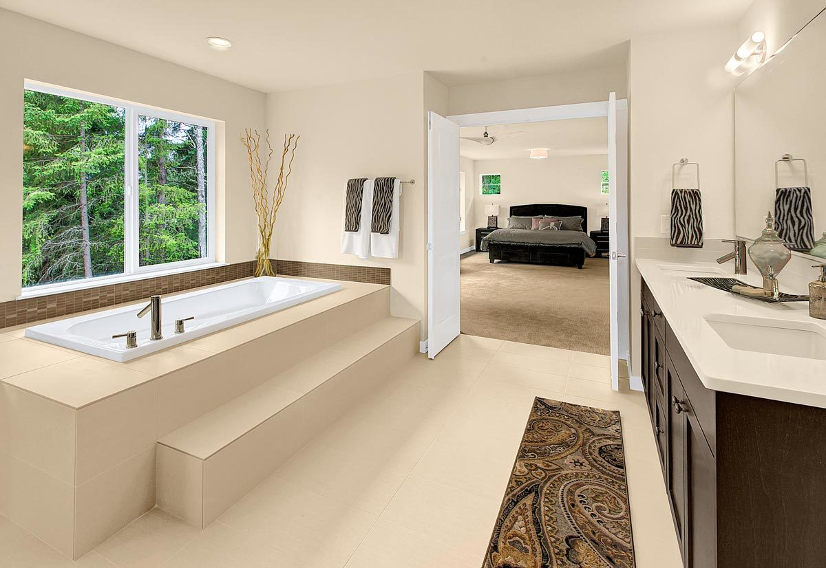 The primary bathroom is equipped with a drop-in bathtub and a dual sink vanity complemented with a patterned runner.