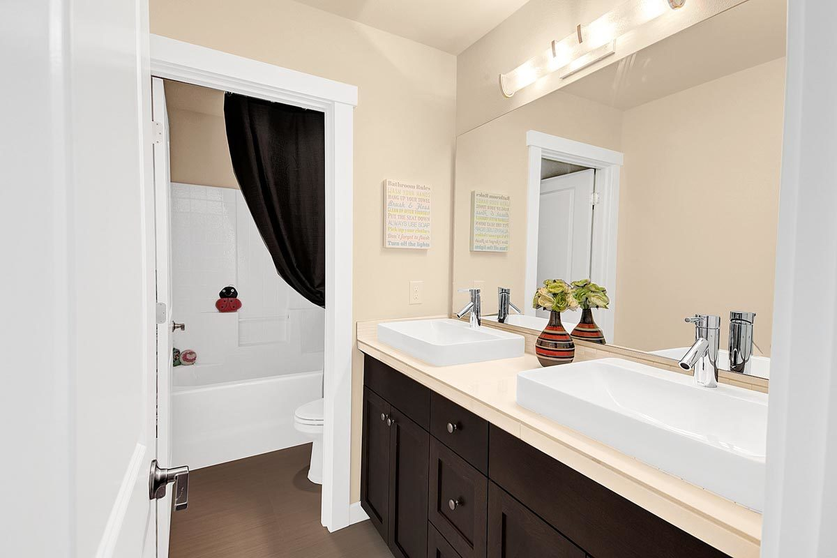 This bathroom offers a dual vessel sink vanity, a toilet, and a tub and shower combo.