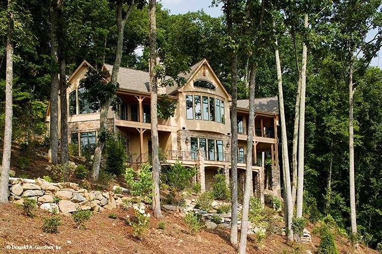 The rear exterior view shows the sloping lot and towering trees that provide privacy to the house.