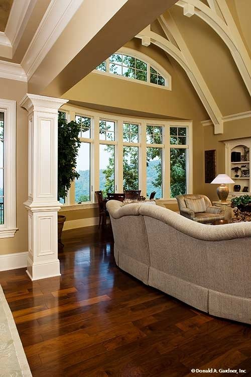 The living room has rich hardwood flooring, a bow window, and a cathedral ceiling lined with decorative white beams.