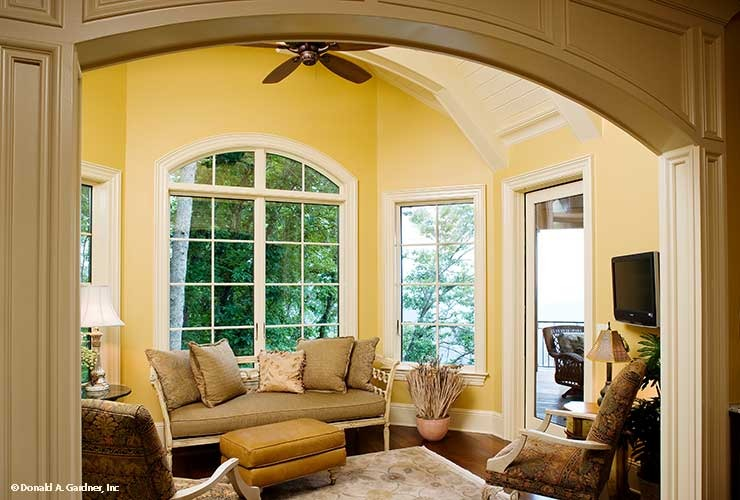 Breakfast room with cozy cushioned seats, leather ottoman, and white framed windows that bring natural light in.