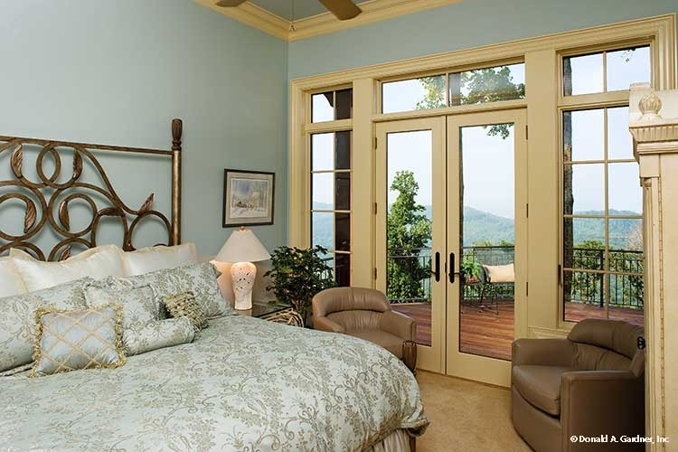 The primary bedroom offers an ornate brass bed, leather round chairs, and a private deck accessible via the french door.