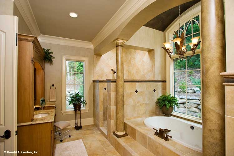 Primary bathroom with a dual sink vanity, walk-in shower, and a deep soaking tub well-lit by a warm chandelier.