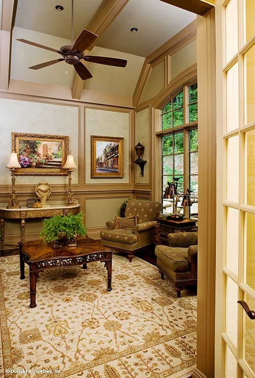 The study has wooden tables, patterned armchairs, and landscape paintings adorning the paneled walls.