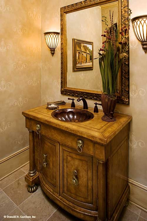 Powder room with wooden vanity and a carved wood mirror flanked by stylish glass sconces.