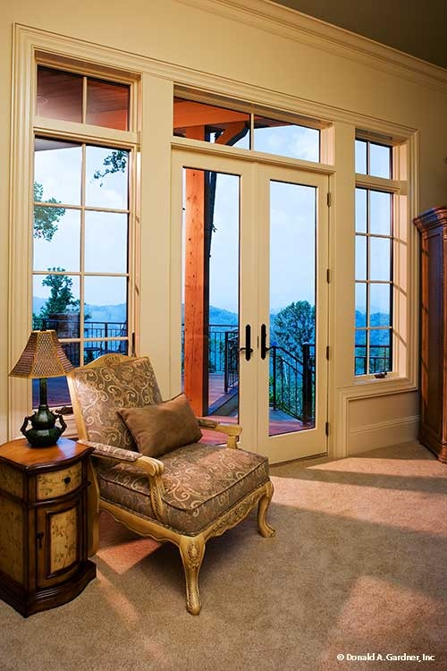 Sitting area with a patterned armchair, wooden side table, and a french door that opens out to the rear deck.