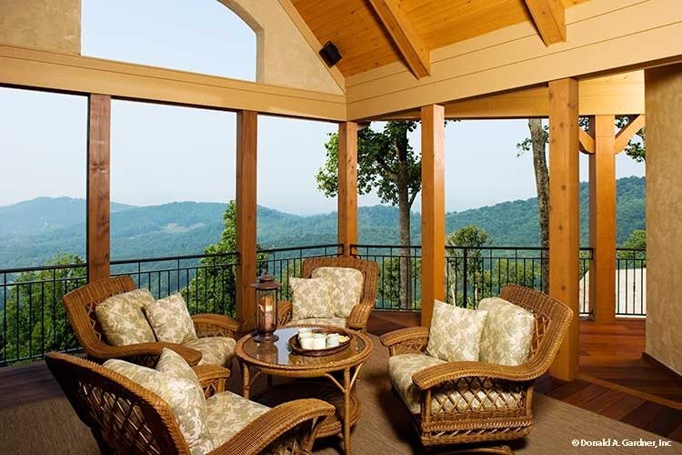 The screened porch showcases wicker armchairs, a matching table, and a breathtaking mountain view.