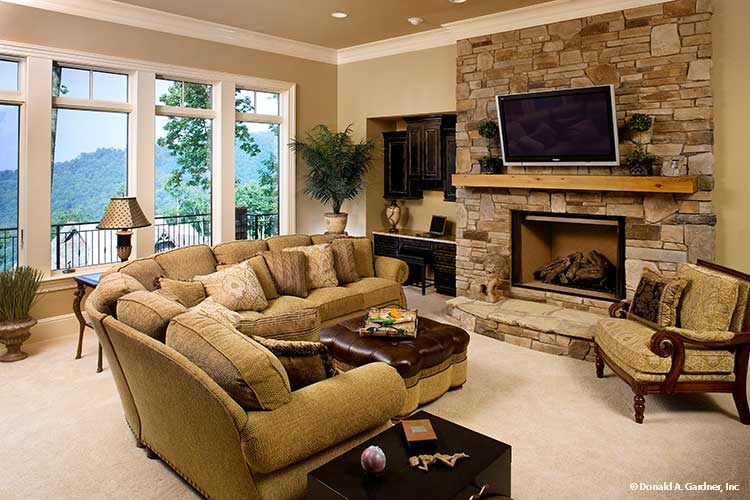 The entertainment room offers an L-shaped sofa, cushioned armchair, and a stone fireplace with a wall-mounted TV on top.