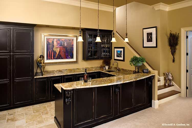 Wet bar with dark wood cabinets, granite countertops, and a two-tier peninsula illuminated by small glass pendants.