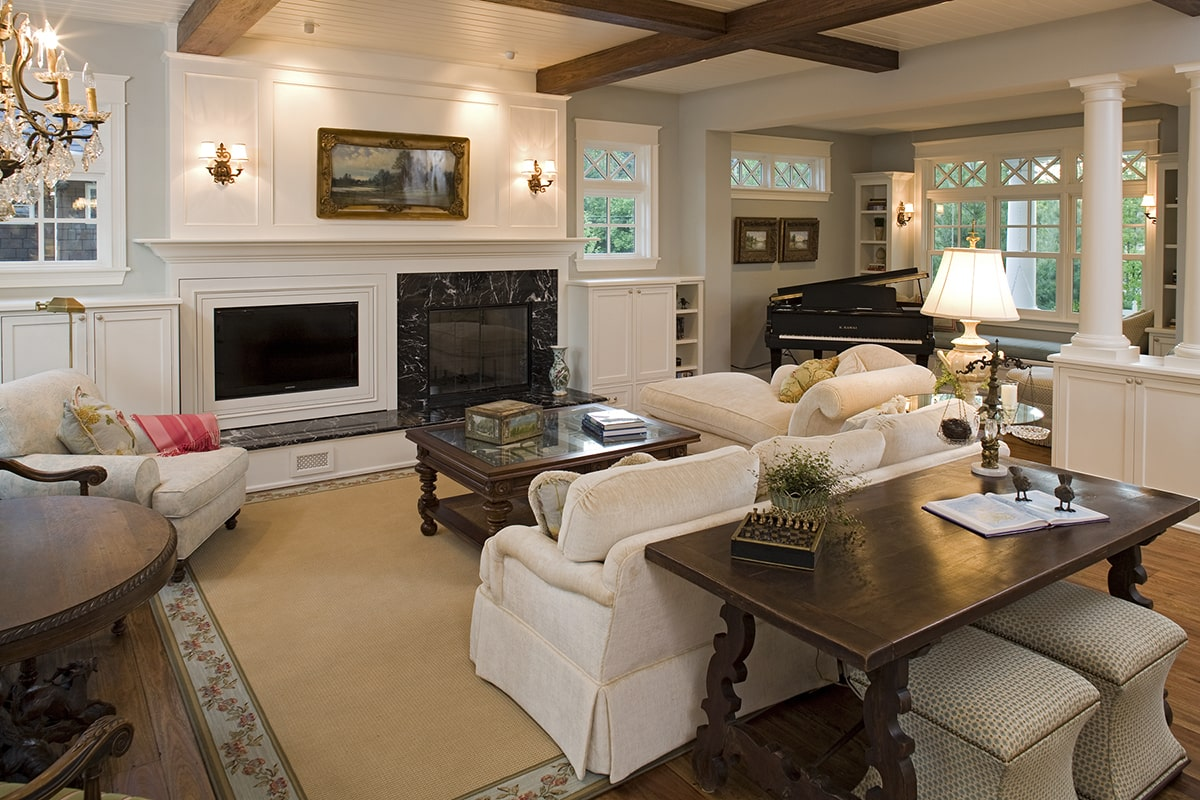 The living room offers beige velvet seats, dark wood tables, a glass-enclosed fireplace, and a baby grand piano near the window seat.