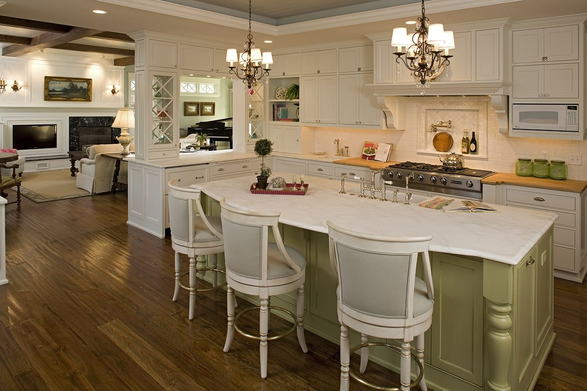 Kitchen with white cabinetry, marble countertops, and a breakfast island well lit by ornate chandeliers.