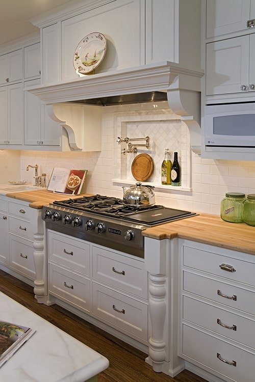There's also a built-in cooktop and a bespoke vent hood adorned with a ceramic plate.