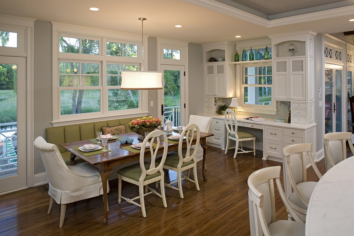 Built-in desk and a dinette offering a wooden dining table, green upholstered bench, and cushioned chairs.