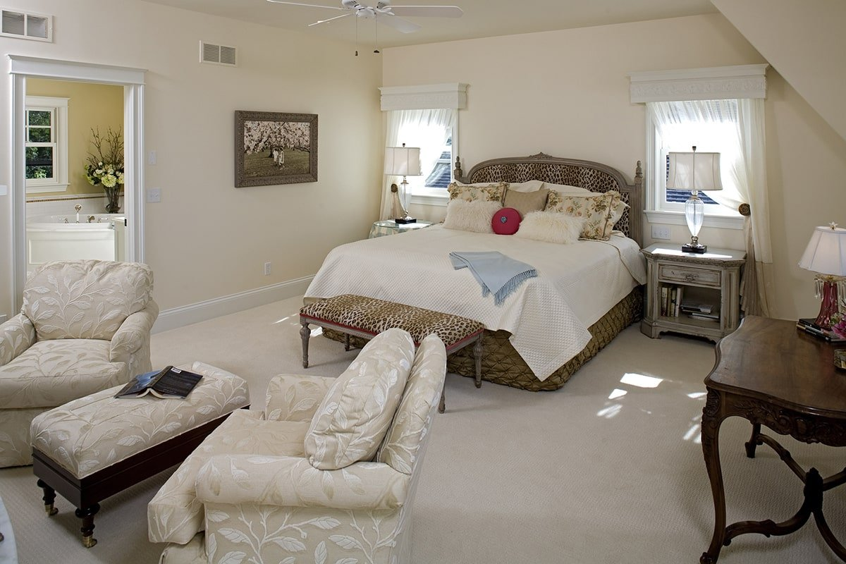 The primary bedroom is furnished with a classy bed, distressed nightstands, a wooden console table, and beige floral chairs paired with a matching ottoman.