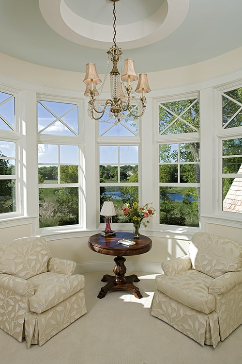 Circular sitting room with skirted armchairs, a round wooden table, beaded chandelier, and magnificent expansive view.
