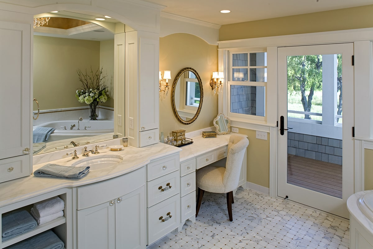 The primary bathroom is equipped with a walk-in shower, white vanities, and a deep soaking tub reflected in the arched mirror.