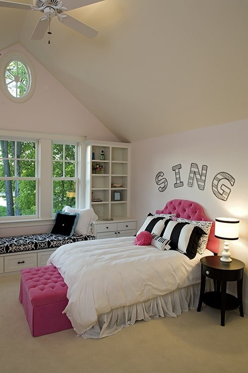 This bedroom showcases a pink tufted bed, window seat, and a white ceiling fan hanging from the cathedral ceiling.