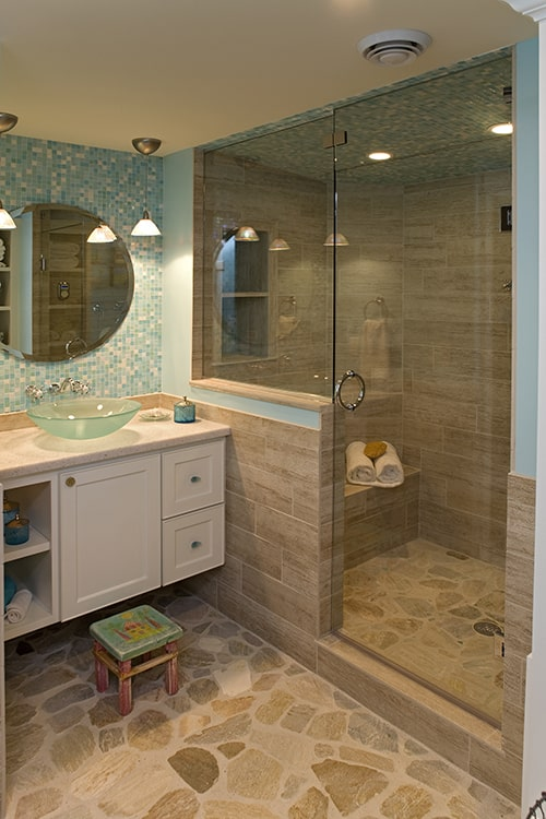 Bathroom with a walk-in shower and a floating vanity topped with a vessel sink and round frameless mirror.