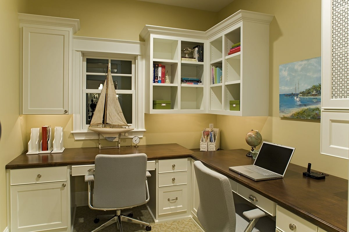 The home office offers white built-ins and two desks paired with gray swivel chairs.