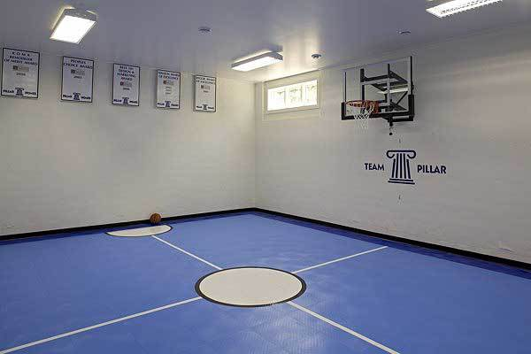 A sports court with blue flooring and a basketball ring fixed against the tempered glass backboard.