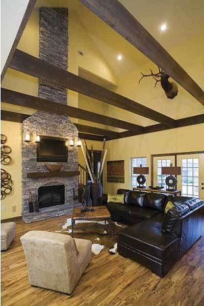 The living room offers an L-shaped leather sofa, beige armchairs, a stone fireplace, and wall-mounted TV.