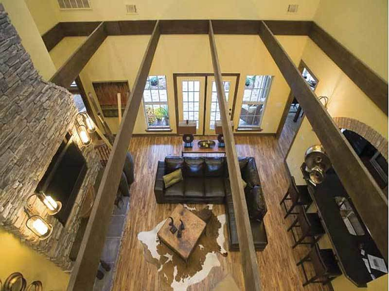 Top view of the living room showing the exposed rustic beams and hardwood flooring topped by a cowhide rug.