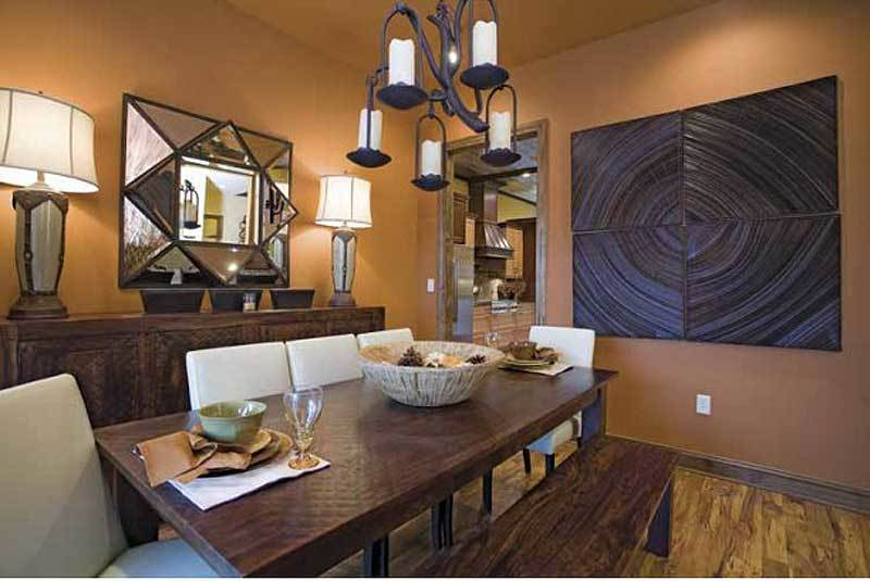 The formal dining room has a wooden dining set, a buffet table, and eye-catching artwork and mirror adorning the brown walls.