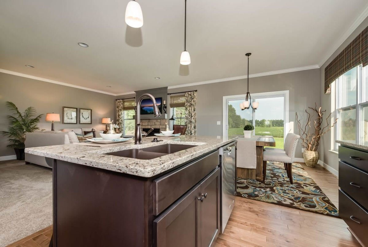 Eat-in kitchen with dark wood cabinets, granite countertops, and an undermount sink fitted on the center island.
