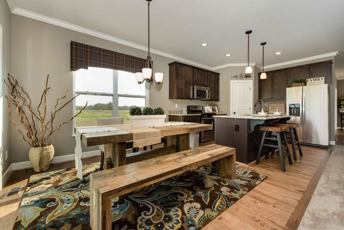 The dining area offers beige upholstered chairs, a wooden dining table, and a matching bench sitting on a patterned area rug.