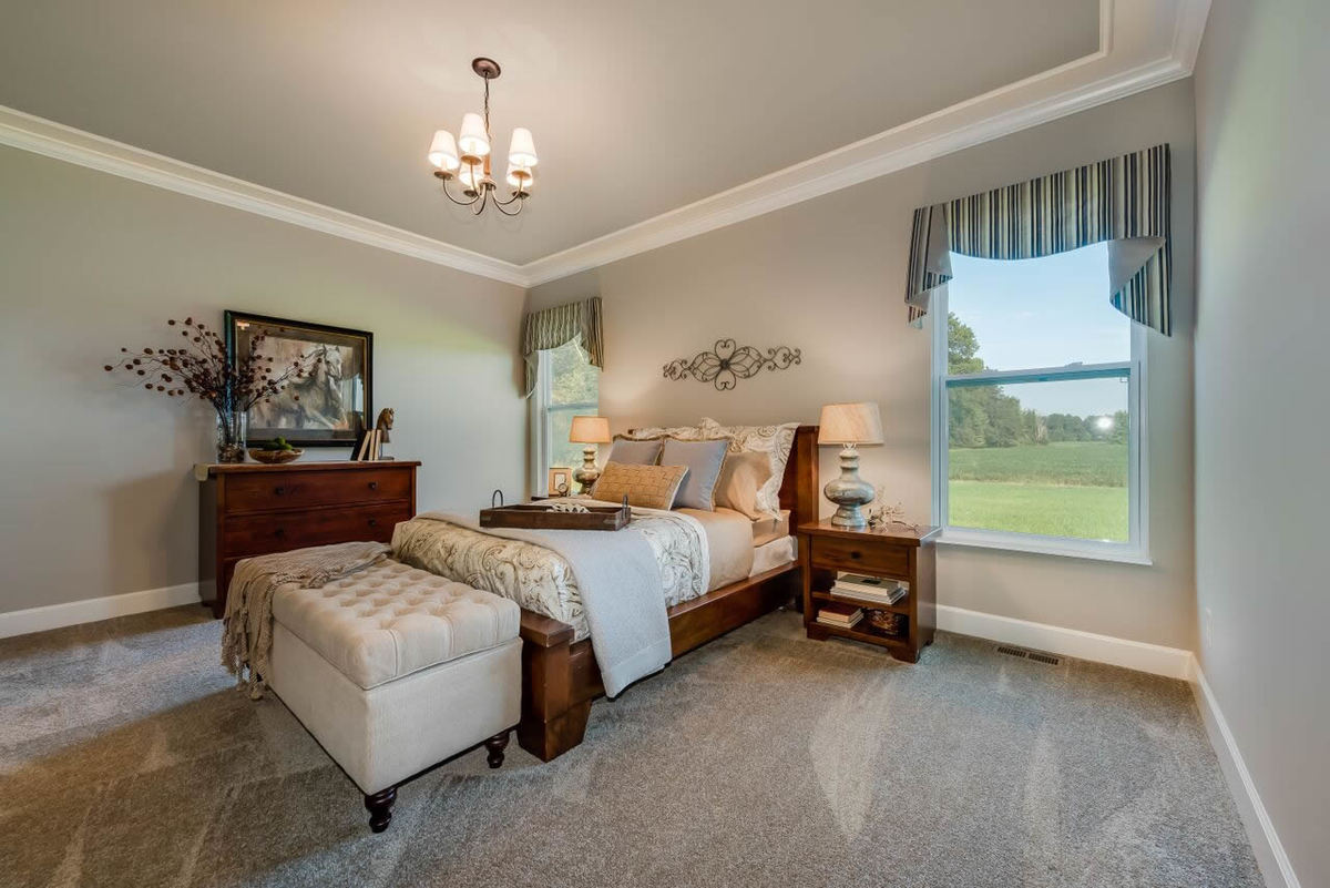 Primary bedroom with wooden furnishings, beige carpet flooring, and white framed windows dressed in striped valances.