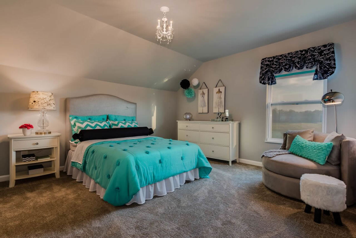 This bedroom has a vaulted ceiling, gray upholstered bed and cuddle chair, furry stool, and a white dresser that matches the nightstand.