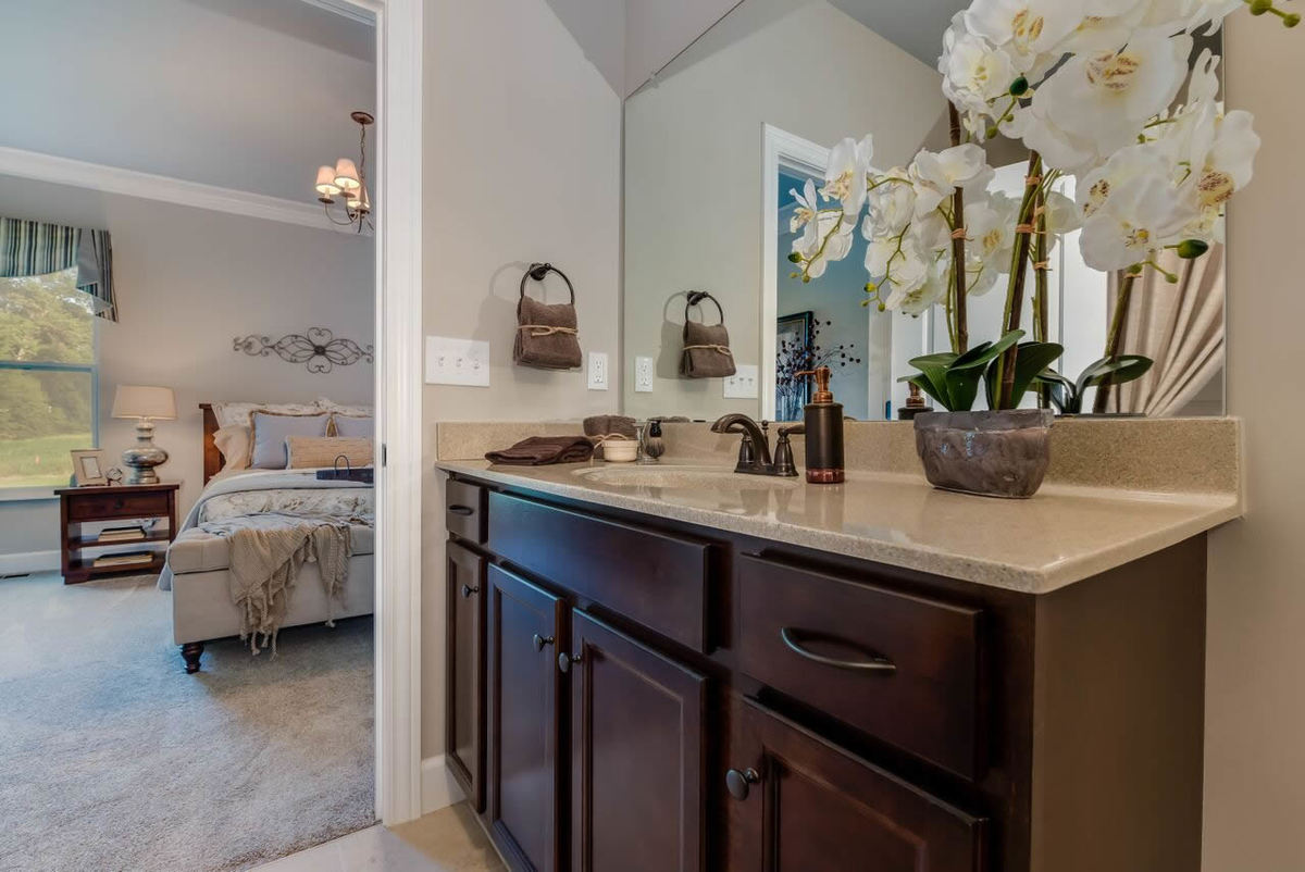 The primary bath features a granite top vanity with dark wood cabinets and a frameless mirror.