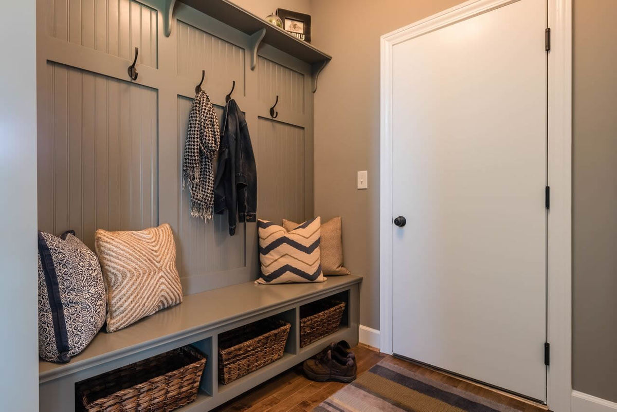 Mudroom with a striped rug, wrought iron coat hooks, and a storage bench topped with various patterned pillows.