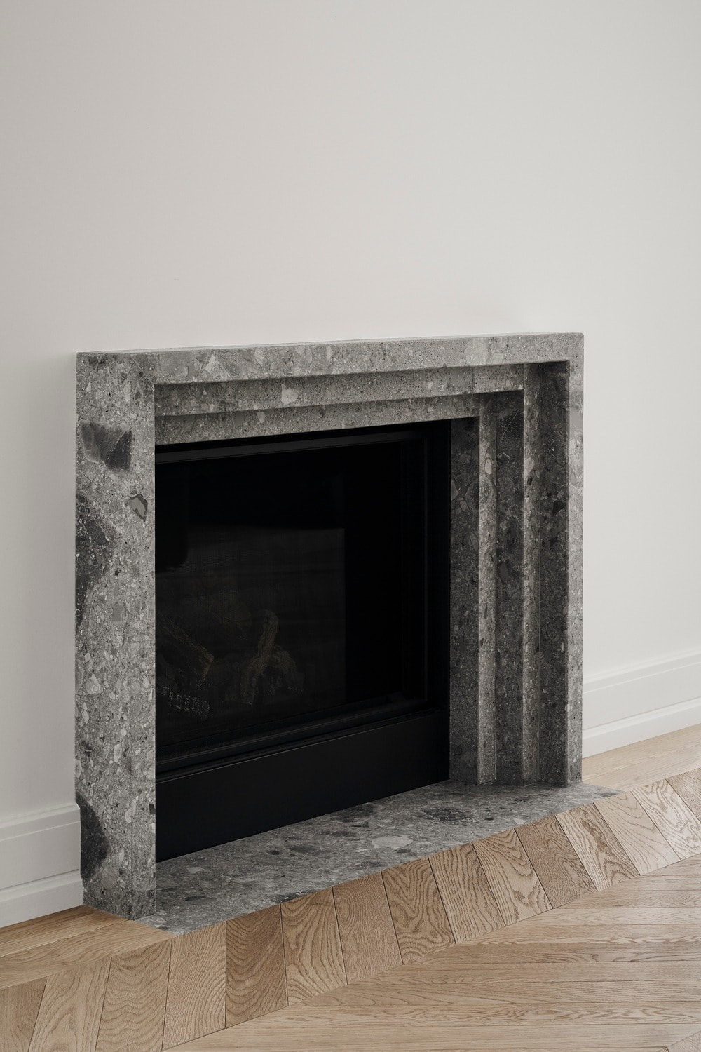 Across from the sofa is this fireplace with a simple concrete mantle that complements the white wall.