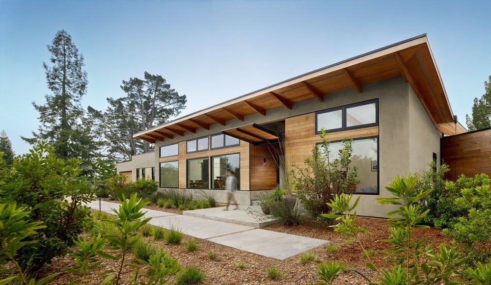 This is the front of the house with wooden exterior walls dominated by large glass walls. These are then complemented by the landscaping that has shrubs and a concrete walkway.