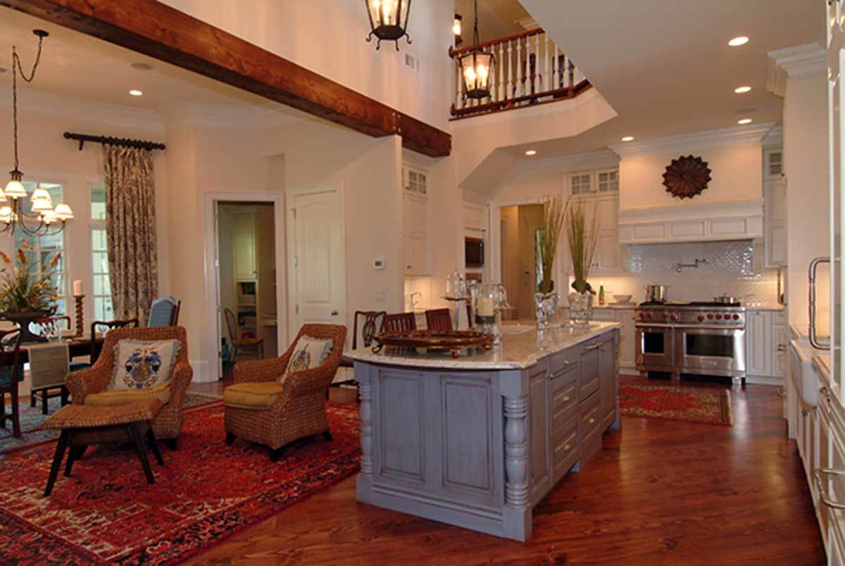 The kitchen is equipped with a double oven range, white cabinetry, and a distressed blue island crowned with a marble countertop.